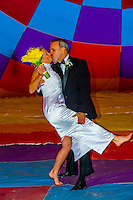 A just married couple pose inside an inflated balloon envelope, Albuquerque International Balloon Fiesta, Albuquerque, New Mexico USA.