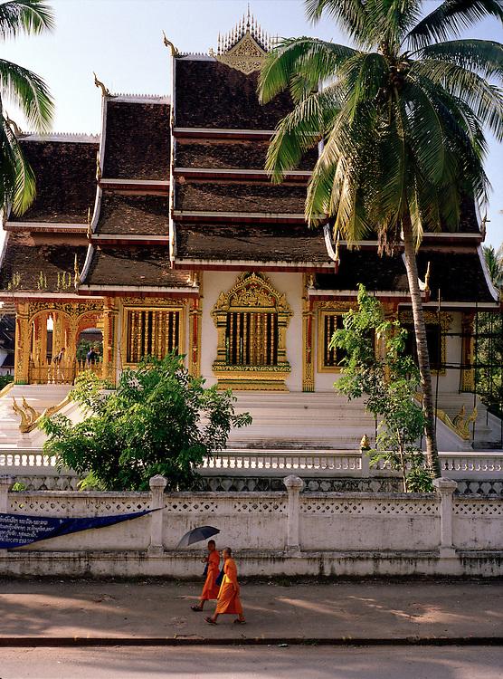 Monks walking past Haw Pha Bang Chapel.