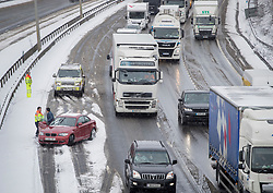 © Licensed to London News Pictures. 27/02/2018. Maidstone, UK.  Traffic Officers help a motorist stranded in the fast lane of the M20 north of Maidstone as snow continues to fall. Freezing temperatures and heavy snow are affecting large parts of Kent.  Photo credit: Peter Macdiarmid/LNP