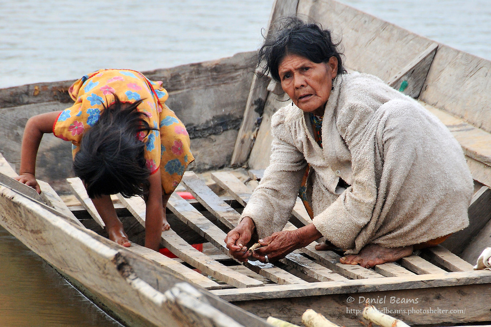 Chimani woman and girl fishing on a boat near San Lorenzo de Moxos, Beni, Bolivia