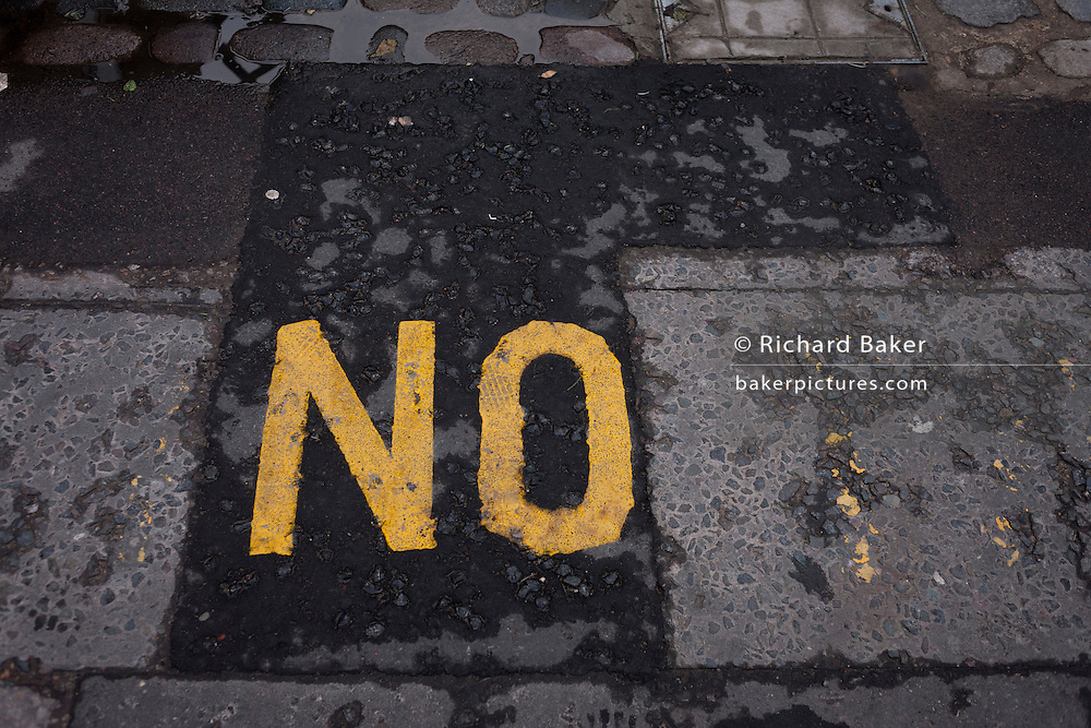 The word NO stencilled on a section of resurfaced tarmac in south London, on 13th January 2017 in London, England.