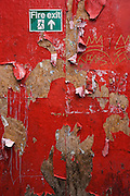 Detail close-up of fire escape sign on a hoarding made from plyboard, with torn paper covering of red material. Caton St,