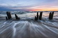 Lake Michigan's waves rush past old pilings at sunset. <br /> Ottawa County, Michigan
