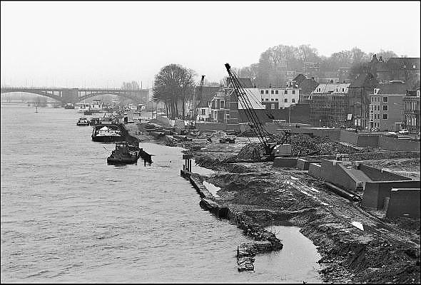 Nederland, Nijmegen, 15-2-1980Reconstructie en herinrichting van de Waalkade en opbouw van de nieuwe benedenstad.In de loop van de 20e eeuw is de kwaliteit van bebouwing in nijmeegse benedenstad zodanig achteruitgegaan dat er grote lege plekken waren ontstaan door gesloopte of ingestorte gebouwen en woningen. Zo stonden langs de Waal in de stad een gasfabriek en electriciteitscentrale. Eind 70er jaren werd besloten dit hele gebied te herbouwen volgens het oude stratenpatroon. Onder druk van de woningnood werden het vooral sociale huurwoningen. Begin jaren 80 is dit voltooid en heeft Nijmegen haar gezicht weer naar de rivier gekeerd. Door het middeleeuwse stratenpatroon en het hoogteverschil is de Benedenstad sinds 1975 een van rijkswege beschermd stadsgezicht.Foto: Flip Franssen/Hollandse Hoogte