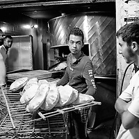 Egypt / Syrian refugees / Syrian men wait for bread as Syrian refugee Nasim El Bokay, 20-years-old, center, works at the El Khier Bakery in the 6th of October City outside of Cairo, Egypt, Monday, May 27, 2013. Nasim who comes from Damascus has been in Egypt for 2 months. He left his family in Syria coming alone to Egypt afraid that he would be taken into the army.  Nasim earns about $170 a month working at the bakery. 'We would like the world to do something to alleviate the suffering of the Syrians inside and outside of Syria'.  / UNHCR / Shawn Baldwin / May 2013