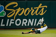 Oakland Athletics center fielder Jaycob Brugman (38) dives for a San Francisco Giants fly ball at Oakland Coliseum in Oakland, California, on July 31, 2017. (Stan Olszewski/Special to S.F. Examiner)