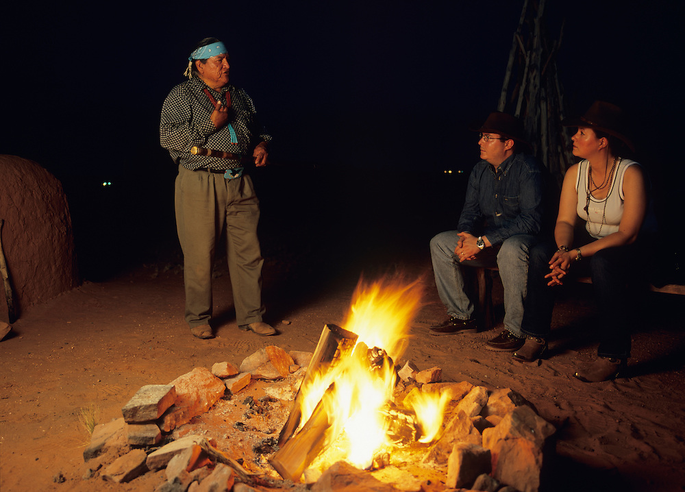 USA, Arizona, Page, Navajo Indian storyteller Wally Brown with tourists by campfire at Navajo Village Heritage Park