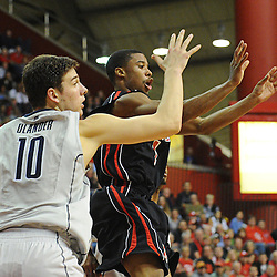 Rutgers Scarlet Knights guard Jerome Seagears (1) passes the ball away from Connecticut Huskies forward Tyler Olander (10) during Rutgers' 67-60 upset victory over #8 UConn in NCAA Big East Basketball action at the Louis Brown Athletic Center in Piscataway, N.J. on Jan 7, 2012.