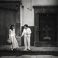 Two woman chatting and cleaning the street in front of their house in San Miguel de Allende