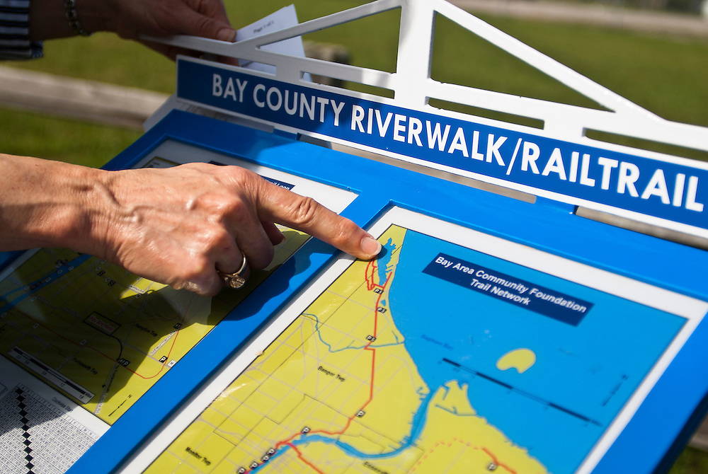 Lathan Goumas | The Bay City Times..Sit Compton, Vice Chair of the Bay Area Community Foundation Riverwalk/Railtrail Committee shows a new sign along the Railtrail in Portsmouth Township, MI., on Tuesday September 27, 2011. The Bay Area Community Foundation recently installed nine new and replaced ten old signs that map out the route of the Riverwalk and Railtrail.