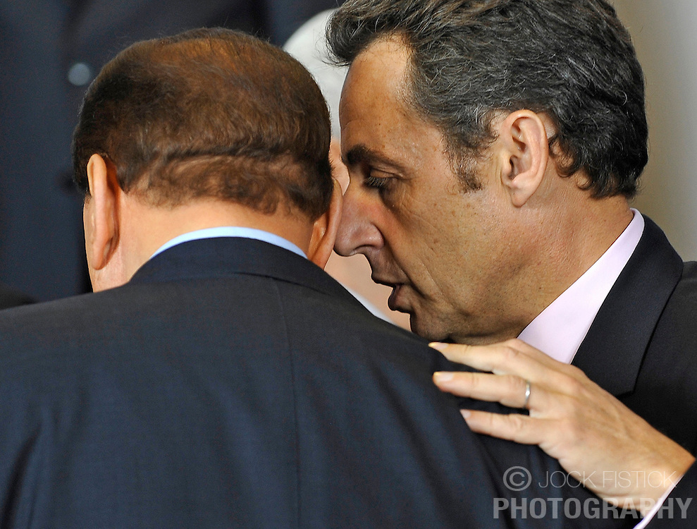 "Nicolas Sarkozy, France's president, right, whispers in the ear of Silvio Berlusconi, Italy's prime minister, during the ""Family Photo"" session at the European Summit, in Brussels, Belgium, Wednesday, Oct. 15, 2008.   (Photo © Jock Fistick)"