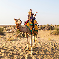 A woman waving and smiling atop a camel she is riding, Thar desert, Rajasthan, India.