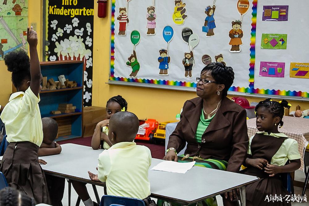 Amiya Joseph raises her hand high in Mrs. Sharon Robles' kindergarten class on the first day of school at Joseph A. Gomez Elementary School. 4 September 2012.  © Aisha-Zakiya Boyd