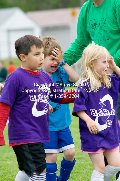 Young soccer players age 7 in tears leaving field with a sports injury. Carondelet Field by Expo School St Paul Minnesota MN USA