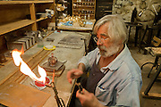Martin lights his torch, preparing to solder a band of crystals onto the based of a crown.