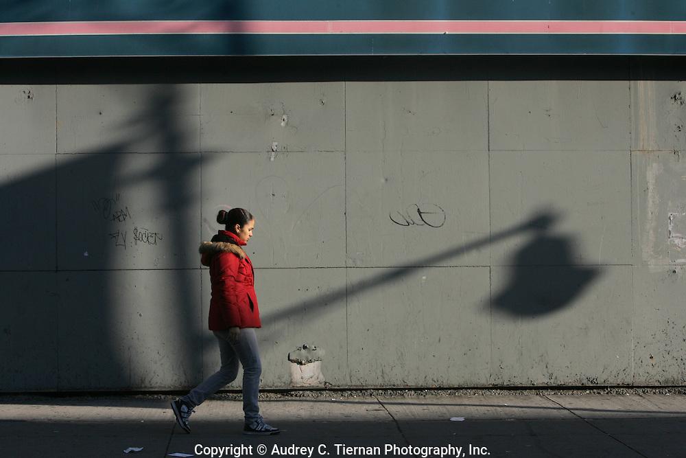 Harlem, NY:  Friday, December 3, 2008-  A woman walks along 116th Street in early morning light.  © Audrey C. Tiernan