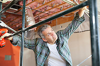 Contractor looking up while standing near scaffolding