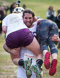 © Licensed to London News Pictures. 06/03/2016. Dorking, UK. Competitor JOEL HICKS carrying two 'wives' while taking part in the 2016 Wife Carrying Race in Dorking, Surrey.  The race, which is run over a course of 380m, with both men and women carry a 'wife' over obstacles,  is believed to have originated in the UK over twelve centuries ago when Viking raiders rampaged into the northeast coast of  England carrying off any unwilling local women .  Photo credit: Ben Cawthra/LNP