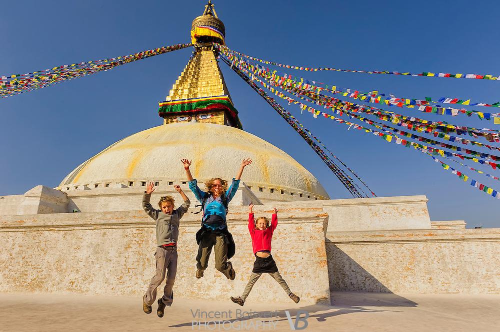 a travelers familly jumping in front of bodnath stupa near kathmandu, nepal