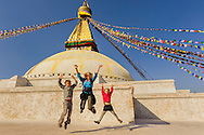 a travelers familly jumping in front of bodnath stupa near kathmandu, nepal