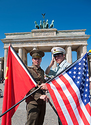 Actors in Soviet and American uniforms posing in-front of Brandenburg Gate in Berlin Germany