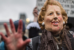 © licensed to London News Pictures. London, UK 13/04/2013. A woman posing with Margaret Thatcher mask as a group of people gathering in Trafalgar Square to celebrate the death of former Prime Minister Margaret Thatcher's death on Saturday, 13 April 2013. Photo credit: Tolga Akmen/LNP