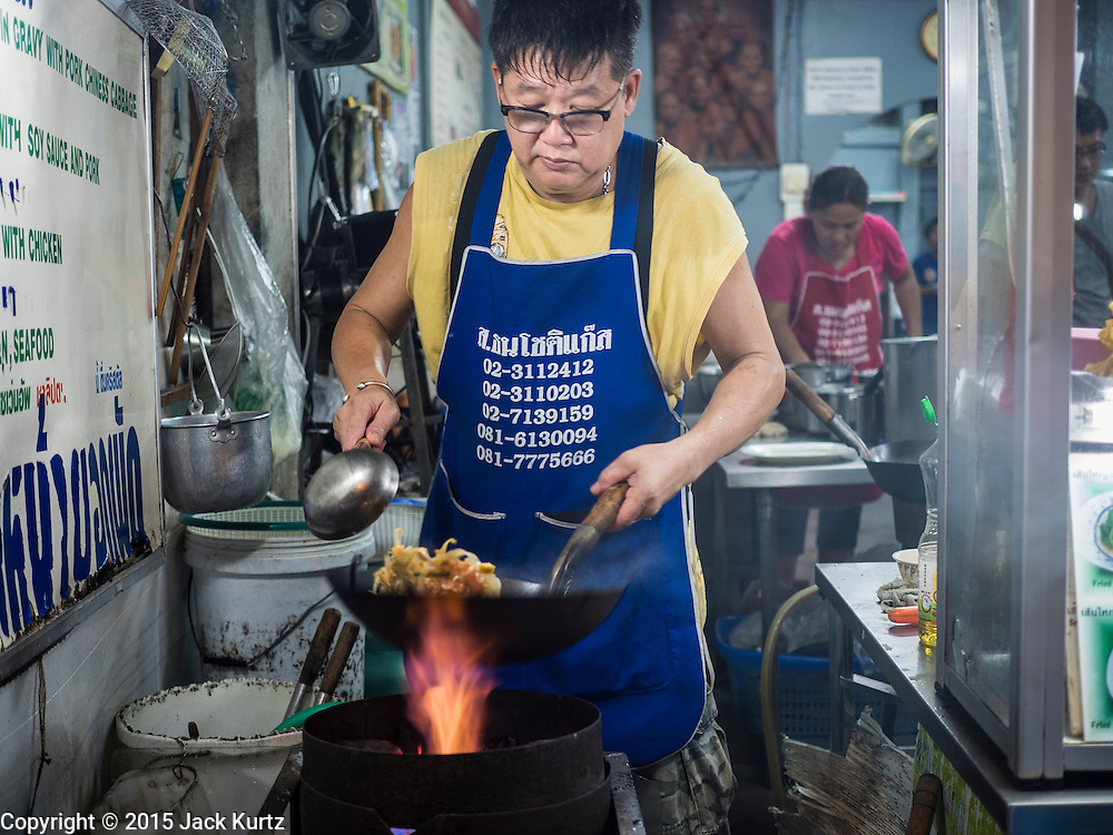 26 MAY 2015 - BANGKOK, THAILAND: A man makes a stir fry at his small restaurant on Sukhumvit Soi 38 in Bangkok. The food carts and small restaurants along Soi 38 have been popular with tourists and Thais alike for more than 40 years. The family that owns the land along the soi recently decided to sell to a condominium developer and not renew the restaurant owners' leases. More than 40 restaurants and food carts will have to close. The first wave of closings could start as soon June 21 and all of the restaurants are supposed to close over the next several months.     PHOTO BY JACK KURTZ