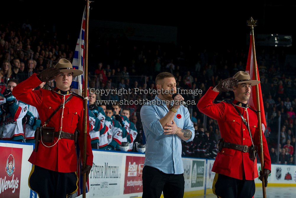 KELOWNA, CANADA - NOVEMBER 11: Jeff Piatelli sings the national anthem between two RCMP officers standing at attention on the ice for Remembrance Day ceremonies at the Kelowna Rockets against the Red Deer Rebels on November 11, 2017 at Prospera Place in Kelowna, British Columbia, Canada.  (Photo by Marissa Baecker/Shoot the Breeze)  *** Local Caption ***