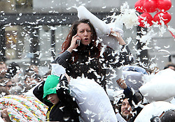 © Licenced to London News Pictures. 05/04/2014. London. UK.  <br /> A pillow fight enthusiast is pictured using her mobile phone during International Pillow Fight Day in Trafalgar Square in London, April 5th 2014. Organised by the Urban Playground Movement, pillow fights take place across various cities in the world today aiming to make events in public spaces become a significant part of popular culture.<br /> Photo Credit: Susannah Ireland