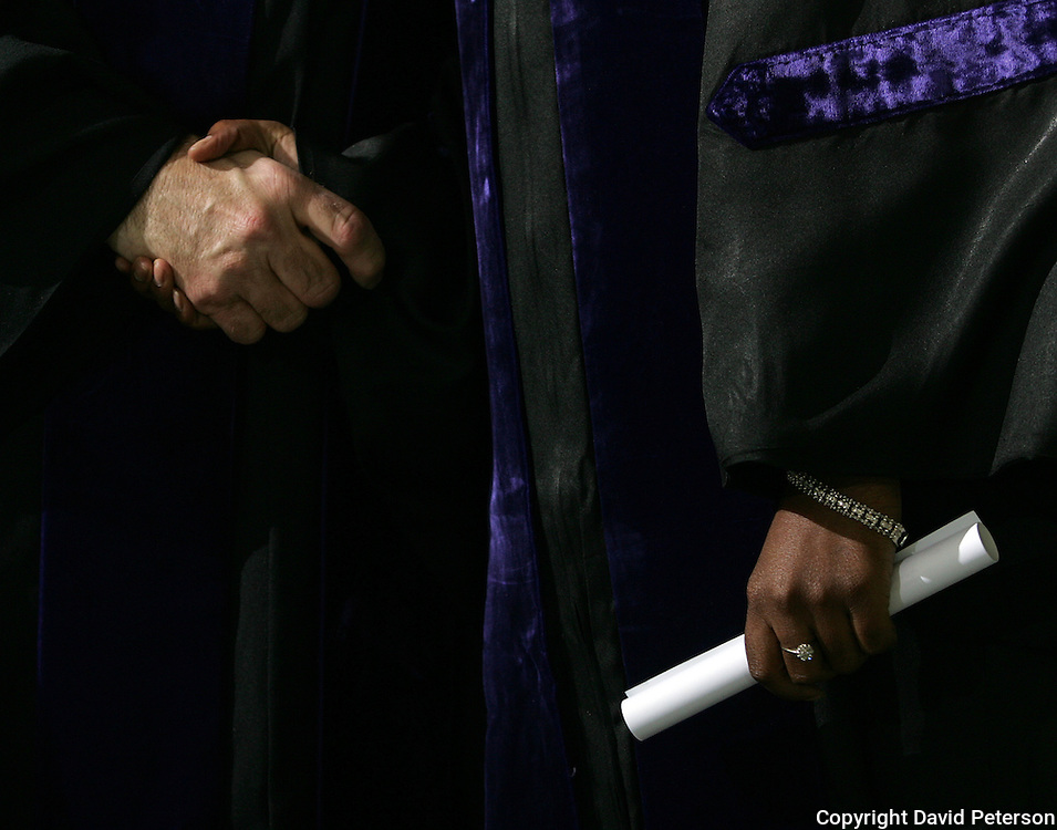 With diploma in hand and a handshake from the school president, a Drake University graduate finishes his career at the private university in Des Moines, Iowa.