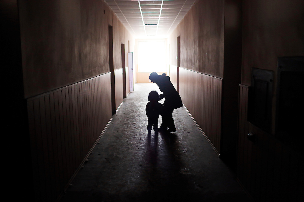 A woman lifts her child in the darkened city administration building while waiting to be evacuated on 5 February, 2015 in Debaltseve, Ukraine.