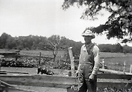 A farmer wearing overalls poses for a photo next to a pig and a fenced in area on a farm during the 1930s somewhere in rural middle America.