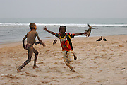 Children playing football on the beach. Celebrating a goal by copying Drogba's goal celebration of the previous evening.  Butre Village. Near Busua. Ghana. West Africa..©Picture Zute Lightfoot.  07939 108077. www.lightfootphoto.co.uk