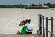 12 JUNE 2013 - YANGON, MYANMAR: A couple spends a private moment on a pier on the bank of the Irrawaddy River in Yangon, Myanmar. The river is popular with young couples late in the afternoon. <br />         PHOTO BY JACK KURTZ