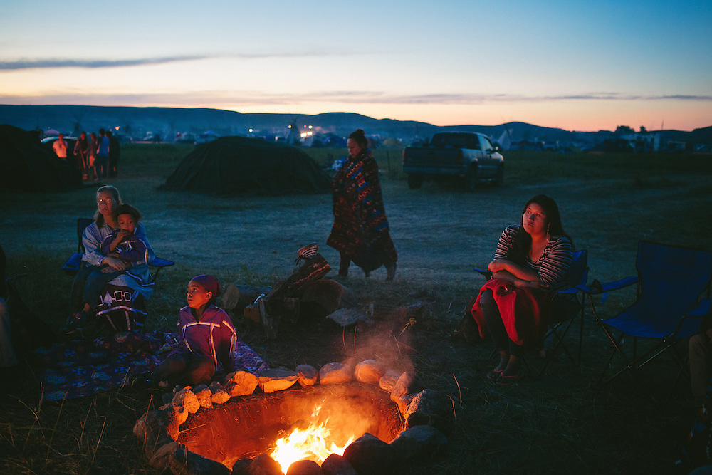 Members of the Onondaga Nation, including Tristyn Jock, at right, listens to a member of her nation speaking about their mission during the on-going protests near the Standing Rock Sioux Reservation.<br /> <br /> <br /> <br /> An arcade of flags whip in the wind, welcoming visitors to the Oceti Sakowin Camp, where thousands have come to protest an oil pipeline. Each banner represents one of the more than 300 Native American tribes that have flocked to North Dakota in what activists are calling the largest, most diverse tribal action in at least a century, perhaps ever. <br /> <br /> In the midst of this historic gathering, a familiar storyline emerges between the U.S. government and the indigenous people who have seen treaties and promises broken repeatedly. Will their efforts and personal sacrifices stop the pipeline? As Donald Trump prepares to take office, many doubt any injunction on construction will stand. <br /> <br /> Still they flock to Oceti Sakowin. They came alone, driving 24 hours straight across the Plains when they saw news on social media about the swelling protest. Some came in caravans with dozens of friends and relatives. They came with the hope that their voices, unified and resolute, would be heard.<br /> <br /> &ldquo;We say &lsquo;mni wiconi&rsquo;: Water is life,&rdquo; said David Archambault II, the chairman of the Standing Rock Sioux, whose reservation sits just south of the pipeline&rsquo;s route. &ldquo;We can&rsquo;t put it at risk, not for just us, but everybody downstream.&rdquo; He added: &ldquo;We&rsquo;re looking out for our future, the children who are not even born yet. What is it they will need? It&rsquo;s water. When we start talking about water, we&rsquo;re talking about the future generations.&rdquo;