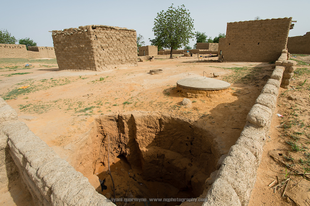A latrine under construction in the village of Gadirga in the Commune of Soukoukoutan in the Dosso Region of Niger on 23 July 2013. The cost of the cement cover (seen on the far side of the pit) is subsidized through a WaterAid program, reducing the cost to the owner from CFA 5000 to CFA 3000. As the edges of the pit have started to collapse due to rainfall while the owner concentrates on farming, a new pit will likely have to be dug.