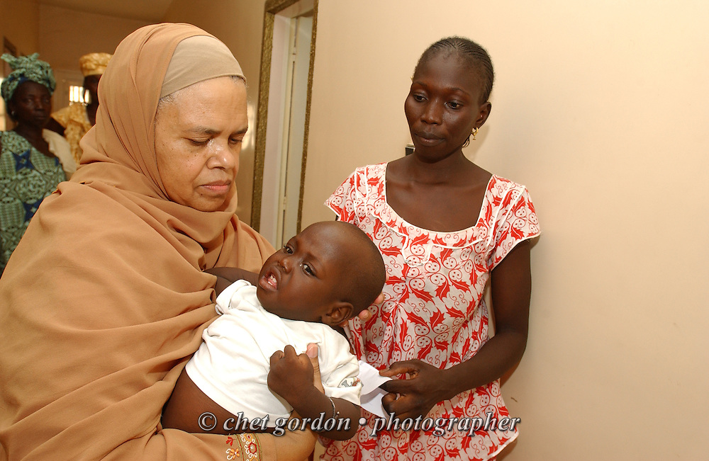 KAOLACK, SENEGAL.  American Muslim medical professional comforts a child at the Shifa Al Asqam Clinic on Wednesday, November 1, 2006.   © Chet Gordon/ THE IMAGE WORKS