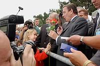 14  AUG 2001, SWINEMUENDE/GERMANY:<br /> Gerhard Schroeder, SPD, Bundeskanzler, bekommt von einem kleinen Maedchen eine Rose, waehrend er zu Fuss die Grenze nach Polen ueberquert, Sommerreise 2001<br /> IMAGE: 20010814-01-007<br /> KEYWORDS: Gerhard Schröder, Kanzlerreise, Kind, child, Swinemünde
