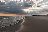 Sunset on ocean beach with rays of lights touching the horizon and outlines of the surf on the sand.  Ocracoke Island, NC - Outer Banks Barrier Island