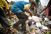 2009-03-13 Jakarta, Indonesia. Kedawung Wetan village in the Tangerang district next to the airport of Jakarta is one of the poorest areas of Jakarta. It&rsquo;s famous for Rawa Kucing, the huge garbage dump. Many adults and children work at the waste site sifting through the rubbish to collect recyclable materials like plastic bags. <br />Other children work at home wrapping bright blue cubes of laundry bleach. A local NGO makes sure the children go to school at least half days. Many do their work still wearing their school uniforms. <br /> <br /> Le village de Kedawung Wetan dans la zone de Tangerang &agrave; c&ocirc;t&eacute; de l'a&eacute;roport est l'une des r&eacute;gions les plus pauvres de Jakarta. Cette zone est connue pour son immense d&eacute;charge  a ciel ouvert : &laquo; Rawa Kucing &raquo;. Beaucoup d'adultes et d'enfants travaillent sur le site de pour rassembler des mat&eacute;riaux recyclables comme par exemple des sacs plastiques. D'autres enfants travaillent chez eux &agrave; envelopper des pastilles de javel. Une O.N.G. locale scolarise les enfants plusieurs heures par jour ou l&rsquo;uniforme est toujours de rigueur.