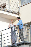 Full length of young business couple conversing at hotel balcony