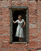 Vintage fashion editorial image of model Brenna Smith in 1940s silk dress and period hair and makeup shot at abandoned Imperial Sugar mill Sugar  Land, Texas by Gerard Harrison Image Theory Photoworks.