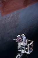 Two People standing in crane bucket Painting Large Ship