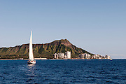 A sailboat sails by Diamond Head Crater in Waikiki.