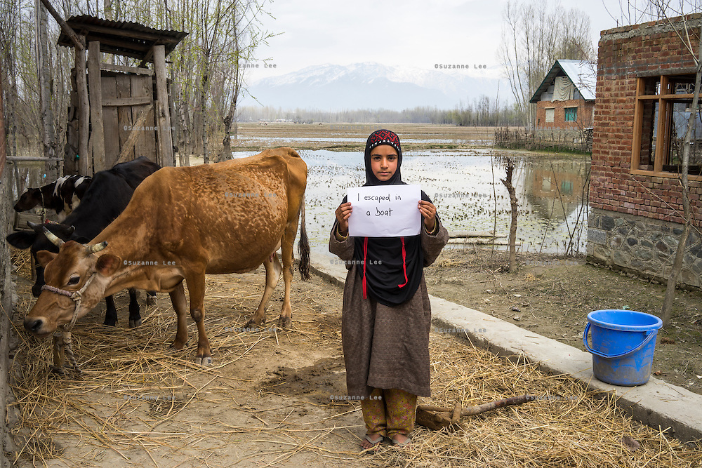 "Apsa Darifa, 10, holds up a sign with the message "" I escaped in a boat"", next to her house which was flooded in September in Purnishadashah village, Jammu and Kashmir, India, on 24th March 2015. Apsa had to flee her house in a boat when the floods came. She had no time to take any of her belongings. Save the Children supported her with an education kit to replace the school books she had lost. Photo by Suzanne Lee for Save the Children"