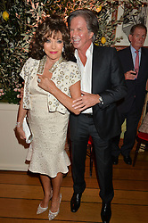 JOAN COLLINS and RICHARD CARING at a party to celebrate 35 years of Harry's Bar, 26 South Audley Street, London on 19th September 2014.