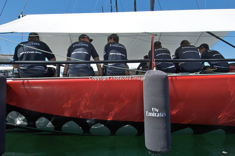 Emirates Team New Zealand sailors huddle under the shade cloth aboard NZL380 before heading out to the race course for day one, Sardinia Trophy, Audi MedCup 21/7/2009