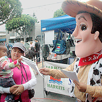 Christopher Andrews in a Woody  costume (Toy Story) hands a flyer to Jan and her daughter Kelani at the Santa Monica Farmers Market on Sunday, October 17 , 2010. Woody was promoting Robinsen Beautilities Halloween Headquarters.