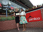 Jennifer Judkins, left, of Longines, presents Katrina Dennis, of Baltimore, Md., with a Longines Conquest Classic timepiece after she wins the Longines Most Elegant Woman at the Preakness contest, Saturday, May 16, 2015, in Baltimore, Md.  Longines, the Swiss watch manufacturer known for its elegant timepieces, is the Official Watch and Timekeeper of the 140th annual Preakness Stakes and the Triple Crown. (Photo by Diane Bondareff/Invision for Longines/AP Images)