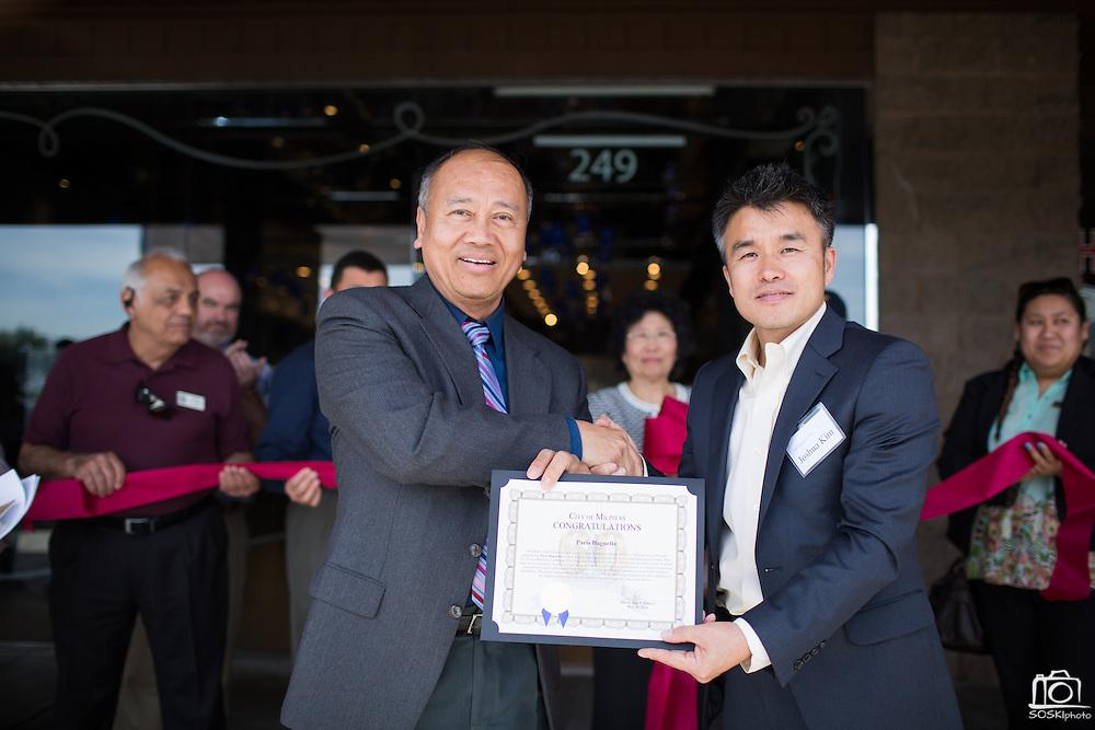 Milpitas Mayor Jose Esteves presents Paris Baguette Cafe Director of Northern California Joshua Kim a certificate of congratulations during the Grand Opening Ribbon Cutting Ceremony at Paris Baguette Cafe in Milpitas, California, on May 16, 2014. (Stan Olszewski/SOSKIphoto)